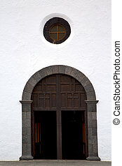 lanzarote  spain canarias     closed wood  church door and white wall abstract