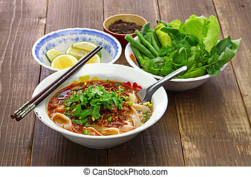 Lao khao soi, wide rice noodles soup with spicy minced pork,...
