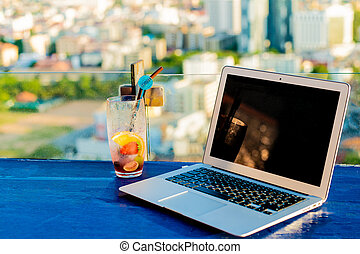 Laptop and glass of summer cocktail on a wooden table, on a bright beautiful panoramic background of the city.