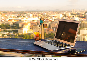 Laptop and glass of summer cocktail on a wooden table, on a bright beautiful panoramic background of the city. mockup