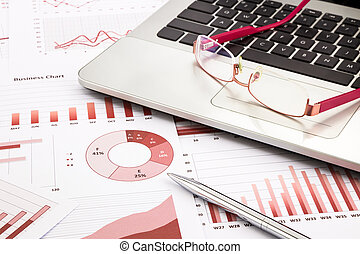 laptop and glasses with red business charts, graphs, research an