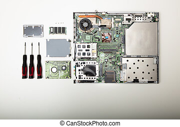 Laptop and precision screwdrivers and parts of computer over white