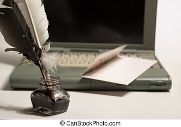 Laptop, feather quill and ink well on white backgrounds