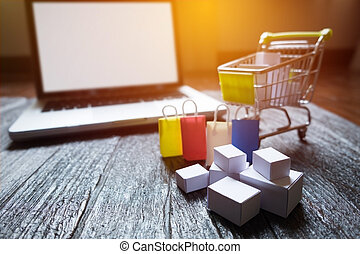 laptop blank screen and hopping cart full of gifts with copyspace, online shopping concept