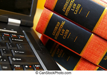 laptop computer and a stack of law books