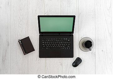 Laptop, computer mouse, cup of coffee and notebook on a wooden table. Top view