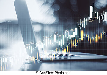 Laptop computer on desktop with forex charts