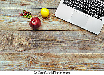 Laptop computer on wooden background with fruits.