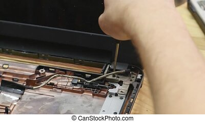 Laptop disassembling in repair shop, close-up. Disassembled computer motherboard on repairman workplace. Electronic development, technology fixing concept