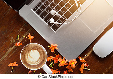 Laptop, earphone and flower with a cup of coffee on old...