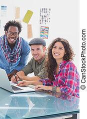 laptop, equipe, criativo, trabalhando, sorrindo, câmera, junto