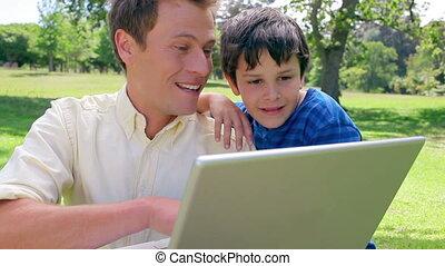 laptop, jego, używając, uśmiechnięty człowiek, syn