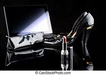 laptop, lipstick and shoes. black background. female set. Online buying cosmetics