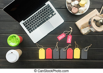 laptop, macarons, coffee and sale tags