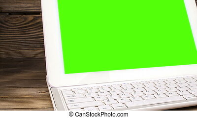 laptop on his desk. Green screen for your custom screen...