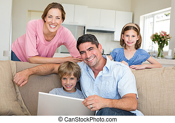 laptop, sentando, usando, sorrindo, quarto familiar
