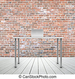 laptop standing on table in brick room