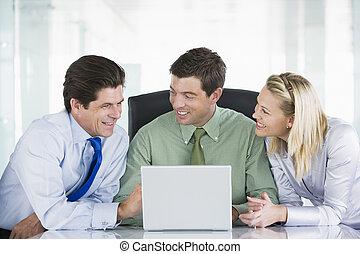 laptop, três, businesspeople, olhar, sala reuniões, sorrindo