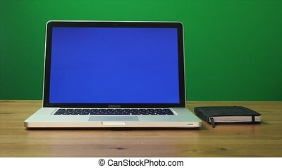 Laptop with a green screen and black notepad on table. Green screen background