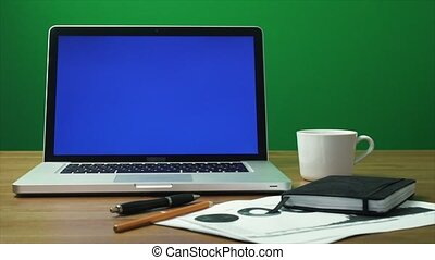 Laptop with a green screen and black notepad on table. Green...