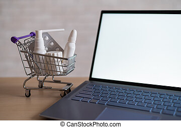 Laptop with blank white screen and miniature shopping cart full of medicines. Online pharmacy concept. Website for buying tablets.