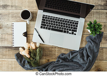 Laptop with diary and coffee cup on wood background