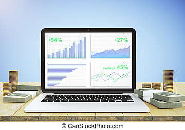 Laptop with financial charts on the wooden table and money