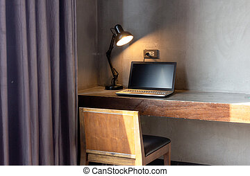 laptop with lamp on table in the room