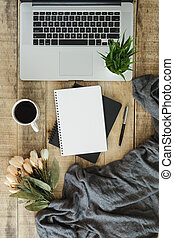Laptop with notebook and coffee cup on wood background