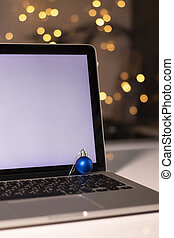 laptop with white screen near New Year's decorations. christmas theme. template