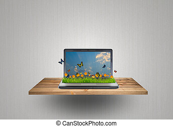 Laptop with yellow flower, grass and butterfly on wood shelf