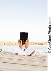 Laptop woman on pier
