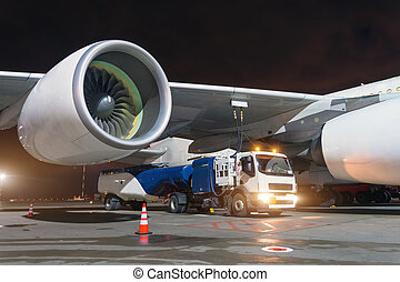 Large aircraft jet engines, Fueling a huge airplane, a truck with fuel with hoses connected to a fuel tank.