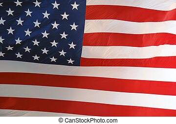 Large American Flag lit by sun - a large american flag flies...