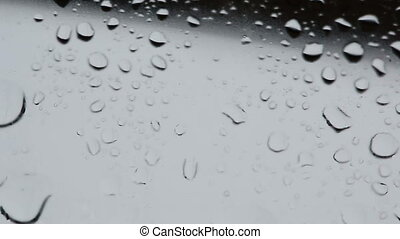 Large and small drops of water on the glass surface.