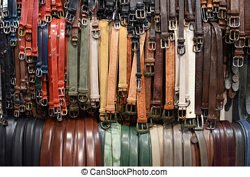 Large assortment of leather belts hung on rails
