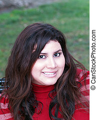 Large attractive woman portrait outdoors red top