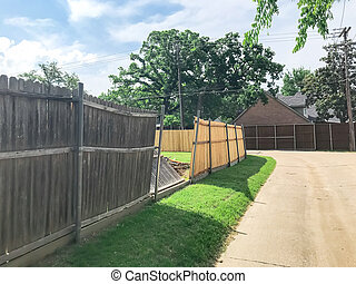 Large backyard of corner house with wooden fence replacement in progress suburbs Dallas, Texas, USA