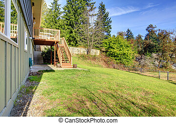Large backyard with deck and house on the hill.