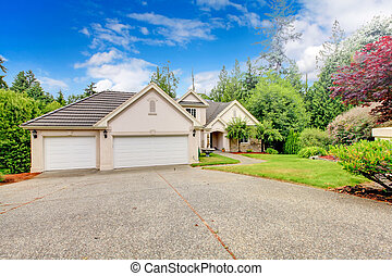 Large beautiful beige and grey house garage exterior during summer.