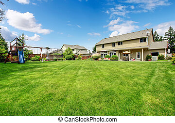 Large beautiful fenced backyard with play ground and nice house.