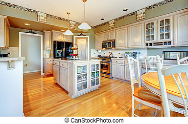 Large beautiful white kitchen with hardwood floor and green...