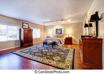 Large bedroom with hardwood floor and two dressers.