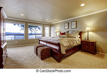 Large bedroom with wood bed and water view.