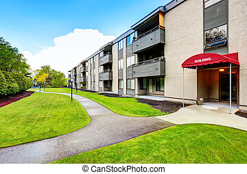 Large beige apartment building with three floors and balconies. Well kept lawn