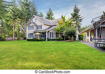 Large beige house with back yard