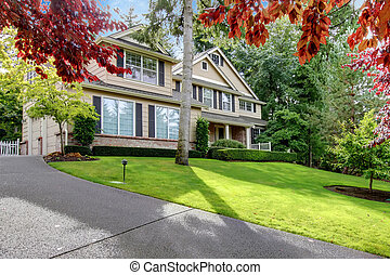 Large beige house w=on the hill with driveway and trees -...