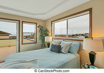 Large beige master bedroom with blue bedding