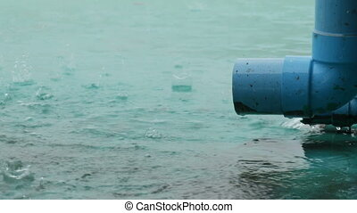 Large blue rain pipe along which the rain drains. Tropical...