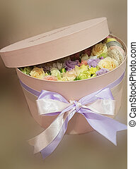 large box with buds of roses of different colors, a soft light background.